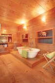 White, free-standing bathtub in wood-panelled bathroom