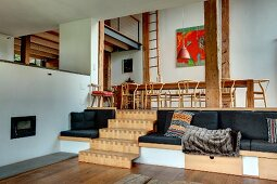 Split-level living area with integrated seating, wooden steps and gallery