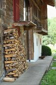 Firewood stacked against weathered wooden façade