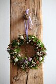 Easter wreath hung on rustic wooden beam