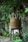 Basket on wooden stool against wall of house