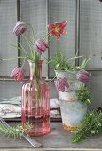 Vintage-style arrangement of stacked zinc pots, snake's head fritillaries in glass vases and sprigs of rosemary