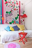 White throw and scatter cushions on couch in front of colourful wall decorated with large floral motifs