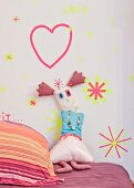 Rag doll leaning against wall decorated with washi-tape shapes
