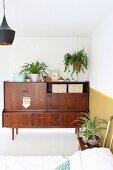 Zimmerpflanzen und Retro Sideboard in Zimmerecke