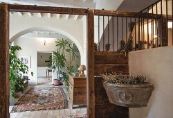 Planted stone sink and arched doorway in hall of restored period building with historical ambiance