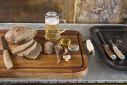 Sliced loaf and beer mug with pewter lid on wooden tray