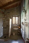 Sloping, wood-beamed ceiling and stone walls in bathroom