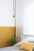 Light-bulb pendant lamp in front of wall with yellow dado