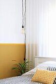 Pendelleuchte mit Glühbirne vor Wand mit gelbem Sockel