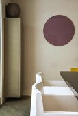 White designer chair below round mauve circle on wall