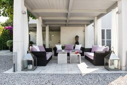 Comfortable black rattan sofas with mauve cushions and scatter cushions on roofed terrace