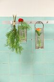 Flowers in small glass bottles attached to graters and hung from row of hooks