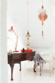 Desk lamp on antique desk, designer chair and suspended ornaments
