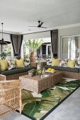Rattan furniture on veranda with jungle-patterned rug