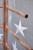 Paper stars hung from stylised Christmas tree hand-made from copper piping