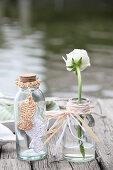 Ranunkel in Glasflasche mit Kranz aus geflochtenen Bastresten und Flasche mit gestrickten Fischen aus Bast