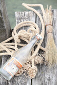 Bügelflasche, Naturkordel und Reisig auf verwittertem Holzsteg