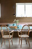 Hand-made wood-veneer bread basket on table and two Windsor chairs