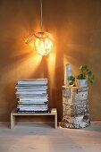 Lampshade made from wood veneer above stacked magazines and tree stump
