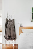 Grey dresses hung from ladder next to bed