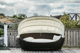 Oval lounger with awning on veranda