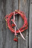 Wreath of twigs with posy of rose hips hung from red and white ribbon on rustic board wall