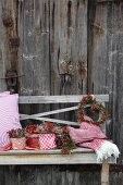 Autumnal flower arrangements and romantic door wreath arranged on rustic wooden bench against board wall