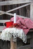 Candlestick decorated with rose hips next to mug arranged on fringed blanket and rustic wooden bench