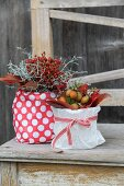 Autumn arrangements of rose hips and autumn leaves in pots wrapped in gift wrap on vintage wooden bench