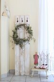Wreath of hops hanging from coat pegs on vintage wooden boards next to angel figurine on stool