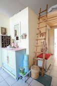 Rustic ladder leading to sleeping platform above doorway next to pastel chest of drawers