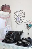 Vintage black typewriters below wire love-hearts on wall used as pinboards
