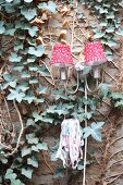 Sconce lamp with red and white lampshades and tealight holder on ivy-covered wall