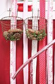 Various pine cones and box sprigs in vintage wire baskets and strips of fabric hung from window frame