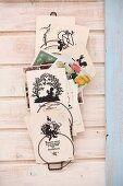 Collection of vintage cards with silhouette motifs in wire rack on wooden wall
