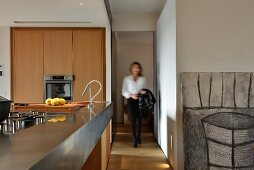 Open-plan, wooden designer kitchen with metal counter and woman in hallway