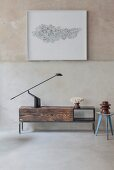 Black table lamp on simple low sideboard made from reclaimed wood below framed artwork