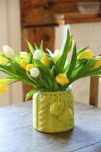 Tulips in vase with knitted cover on old wooden table