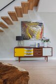 Abstract artwork above retro sideboard with colourful doors