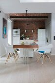 Modern dining table in open-plan kitchen with brick wall and vaulted ceiling
