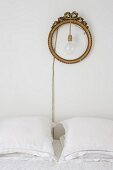 Pendant lamp hung in round gilt frame above bed