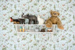Vintage-style toys on shelves mounted on floral wallpaper