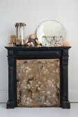 Torn fire screen in front of old fireplace with vintage ornaments on mantelpiece