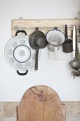 Old kitchen utensils hung from board on wall
