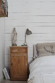 Bed against wall clad in white-painted boards