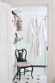 Dressing gown hung on wall of shower above old chair