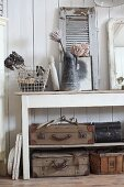 Old suitcases on shelves below console table decorated with vintage ornaments and jug of proteas