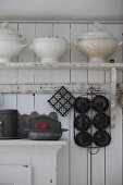 Old soup tureens on bracket shelf on white board wall