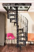 Pink retro chair next to black cast iron spiral staircase